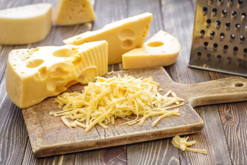 Various pieces of cheese and some grated cheese, with a grater