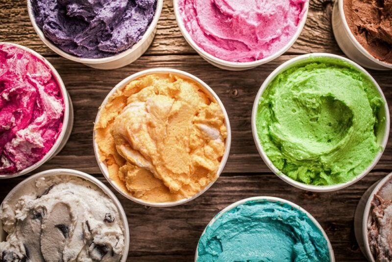 Small pottles of ice cream in various colors, including green, pink, purple and orange