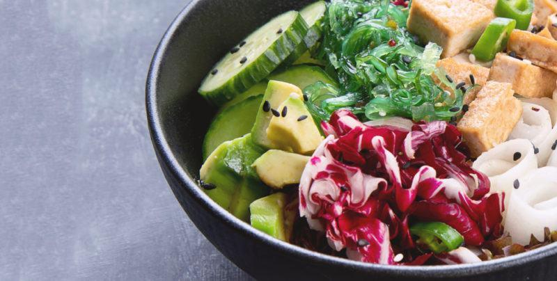 A black bowl with vegan ingredients and seaweed