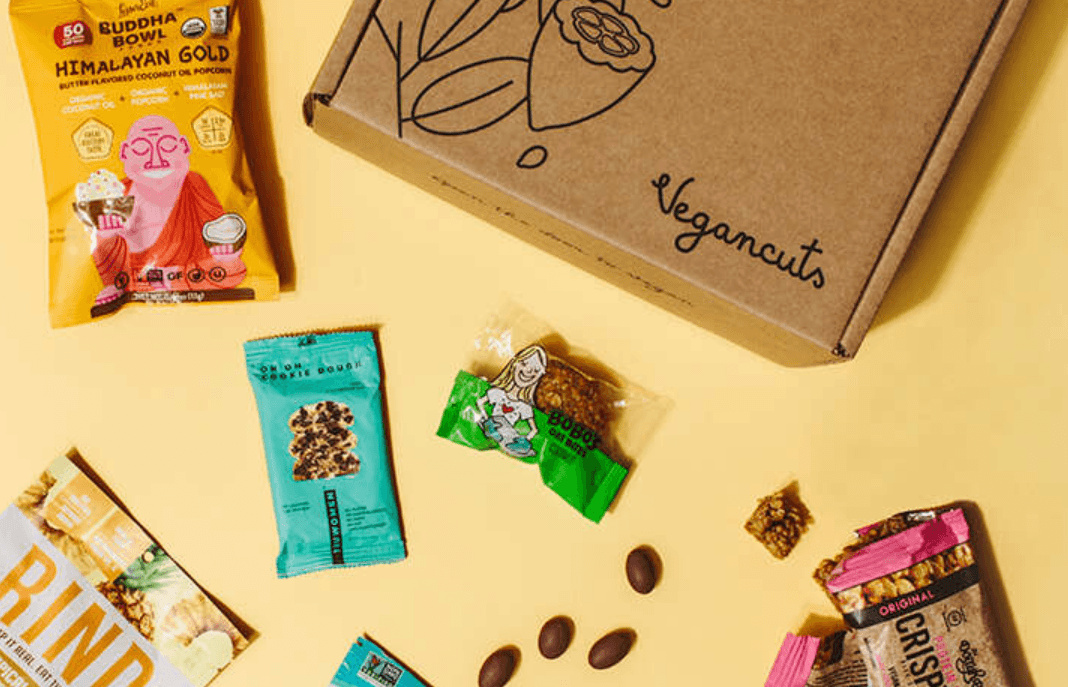 Yellow background, with scattered vegan snacks on the table and in the upper right corner is the vegancuts brown cardboard box, that says vegan cuts and an outline illustration of plants