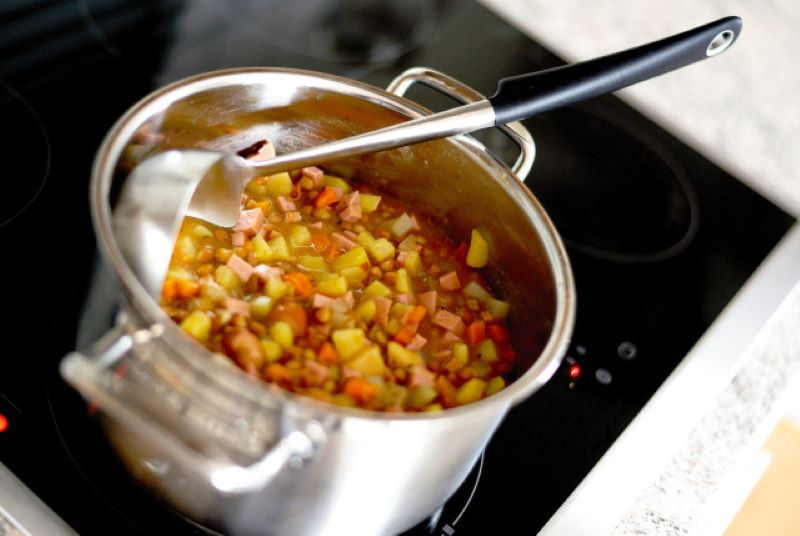 Silver double handled pot of soup sitting on a stove top with a black handled silver ladle on top.  The soup in the pot is vegetable, ham, and bean.