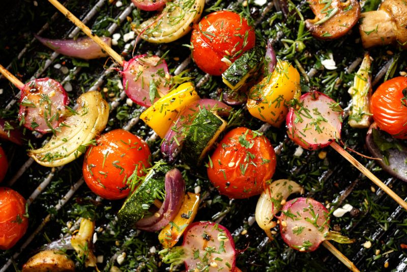 A selection of vegetables on skewers on a grill