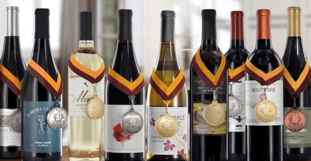 nine bottles of wine with medals hanging on each one the wines vary in type includes both white and red wine