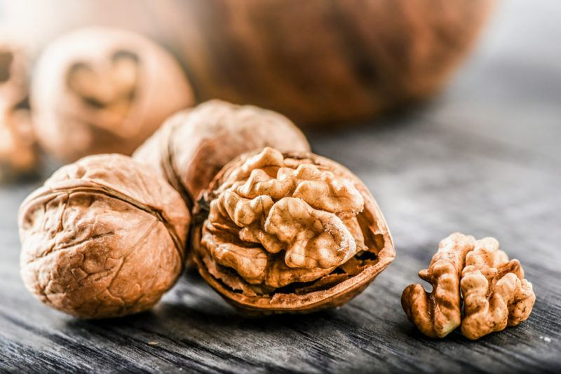 A handful of walnuts, one of which has been split open