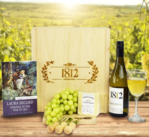 Wooden board with wine, cheese, grapes and a book