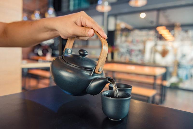 Warm water being poured into a black cup from a teapot