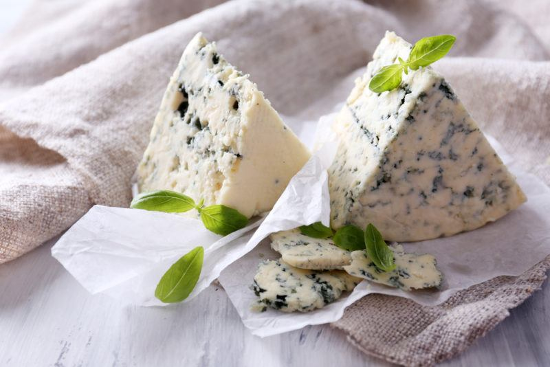 Wedges of blue cheese on paper and marble