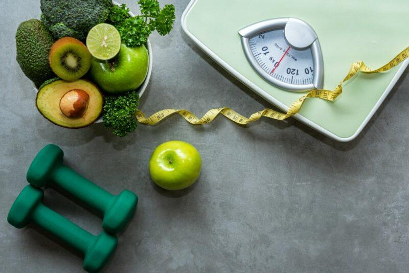 A scale, a tape measure, two hand weights and fresh fruits