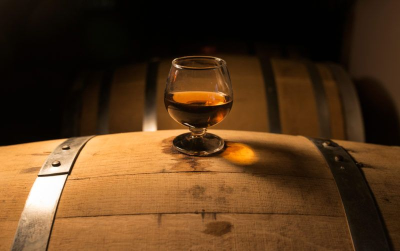 A glass of whiskey on top of an oak barrel