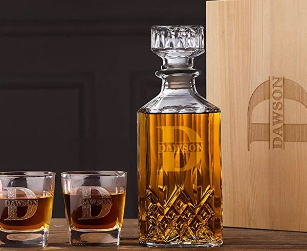 Monogrammed whiskey decanter, glasses and box on a wooden table