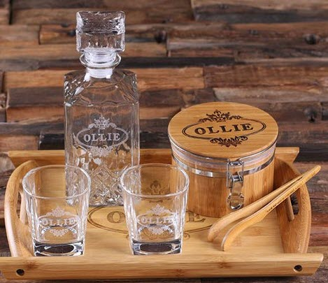 Wooden tray with an engraved set of whiskey decanter, glasses, ice bucket and tongs.