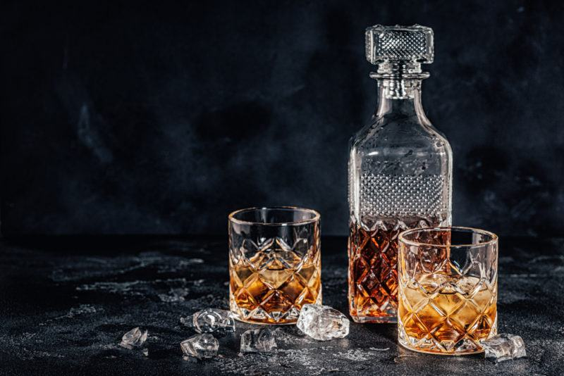 Whiskey in a Decanter with Two Glasses against a black table and background