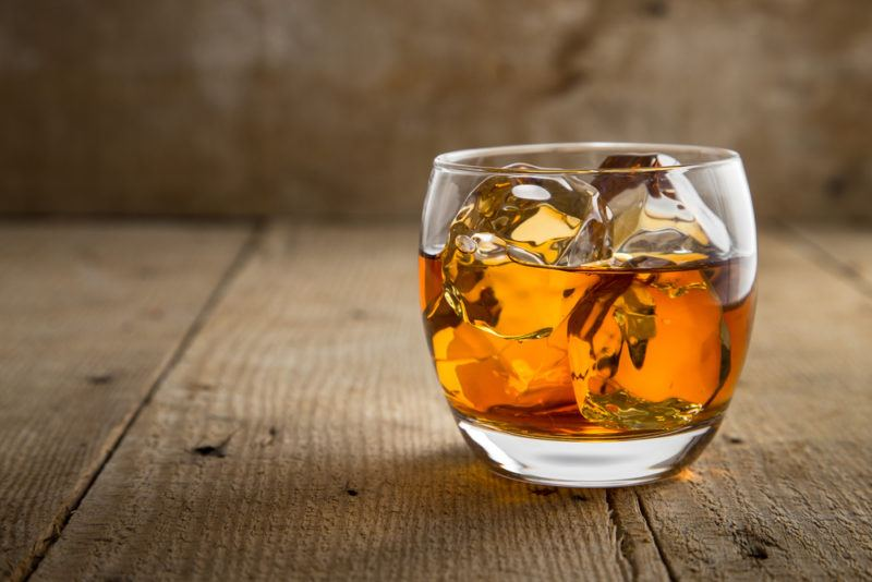 Whiskey in a glass with plenty of ice on a wooden table