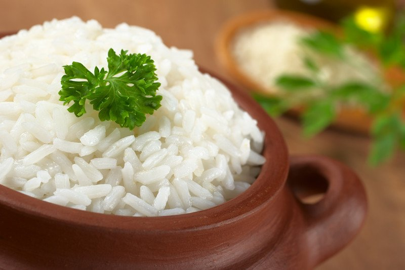 A brown bowl is filled with cooked white rice with a sprig of parsley as a garnish.