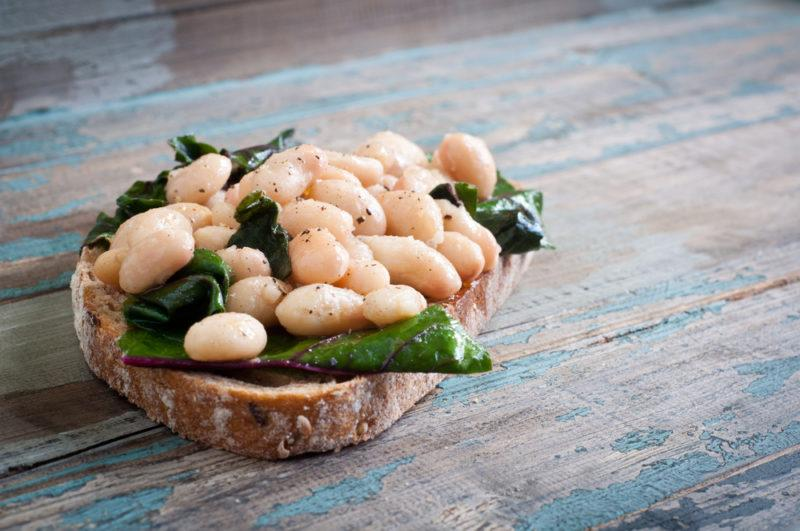 A piece of toast or bread with white beans and spinach