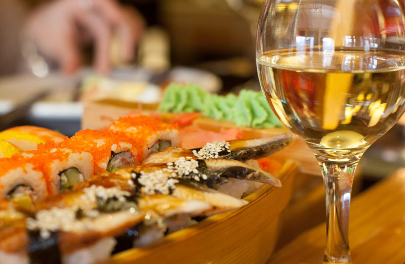 A wooden board with sushi next to a glass of wine