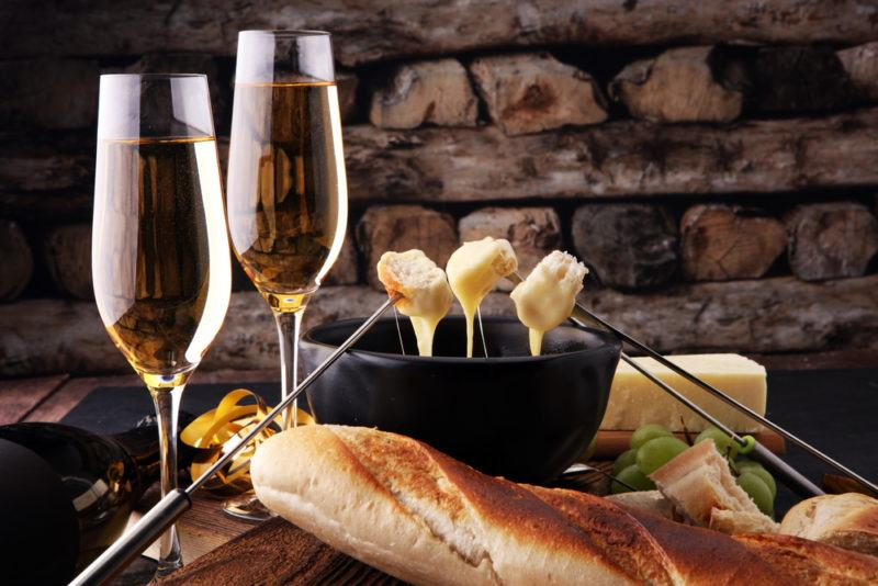 Two glasses of champagne next to a black fondue pot
