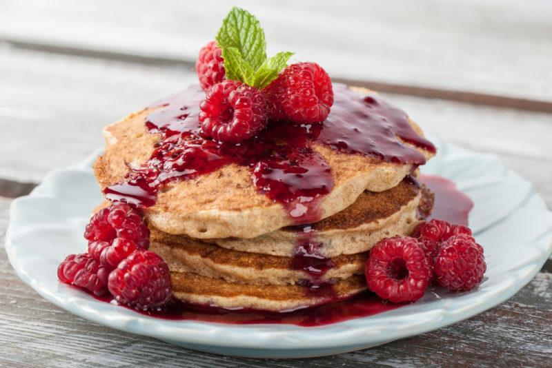 A stack of whole grain pancakes, with berries and sauce