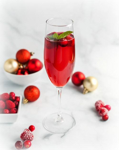 A tall wine glass with a red cocktail and cranberries