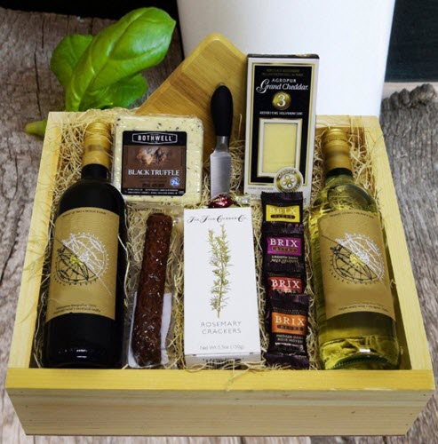 A gift crate containing 2 bottles of wine, cheese, chocolates and sausage.