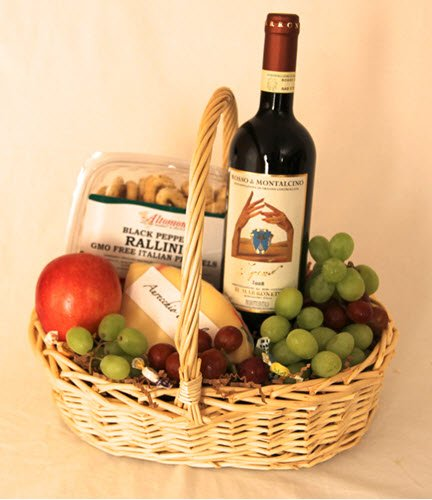 A small basket with wine, cheese and grapes
