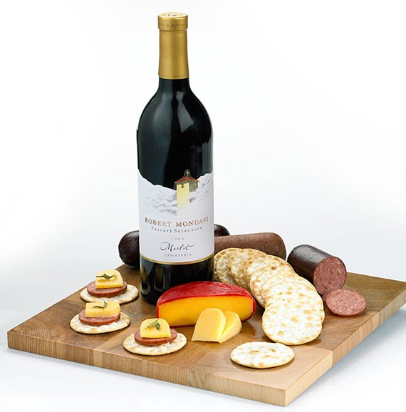 A bread board with a selection of wine, cheese and crackers.