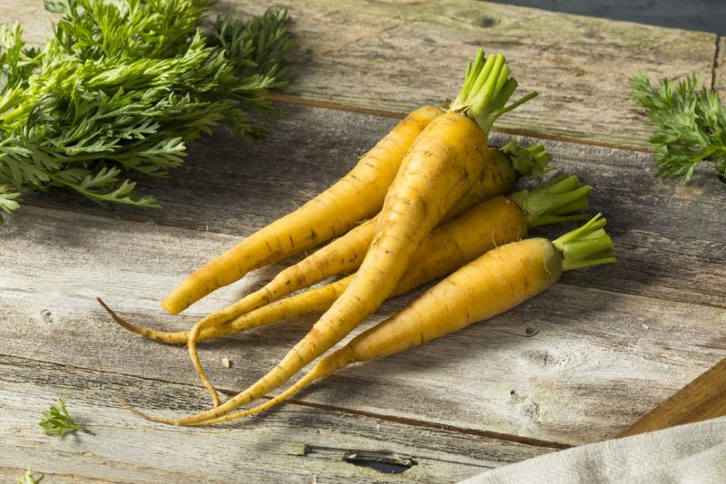 A handful of yellow carrots on a wooden board