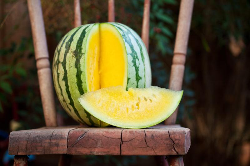 Yellow watermelon with a piece cut out of it