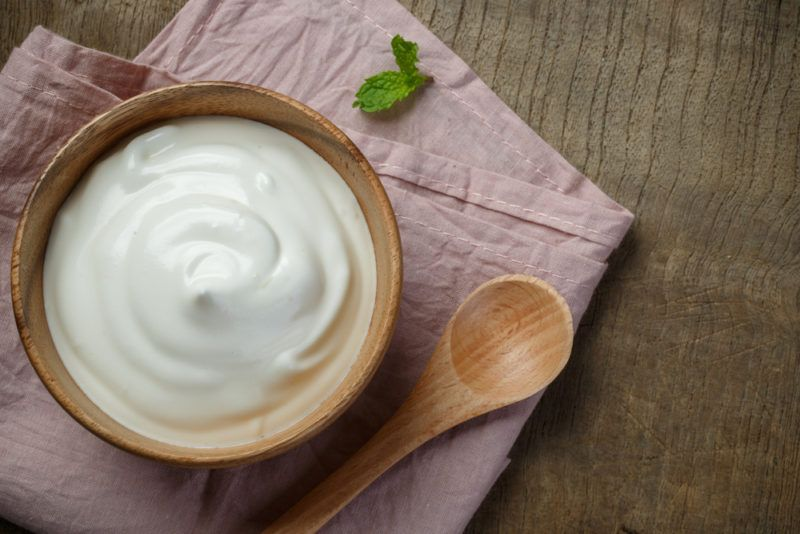 A wooden bowl of yogurt and a spoon