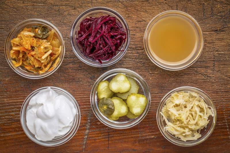 This photo shows an overhead view of six open jars of fermented foods, including kimchi, beets, apple cider vinegar, yogurt, and sauerkraut.