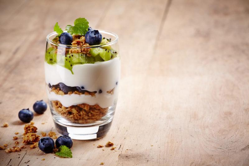 A glass containing yogurt parfait and granola