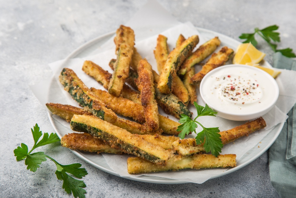 A white plate filled with zucchini fries and a bowl of white dip