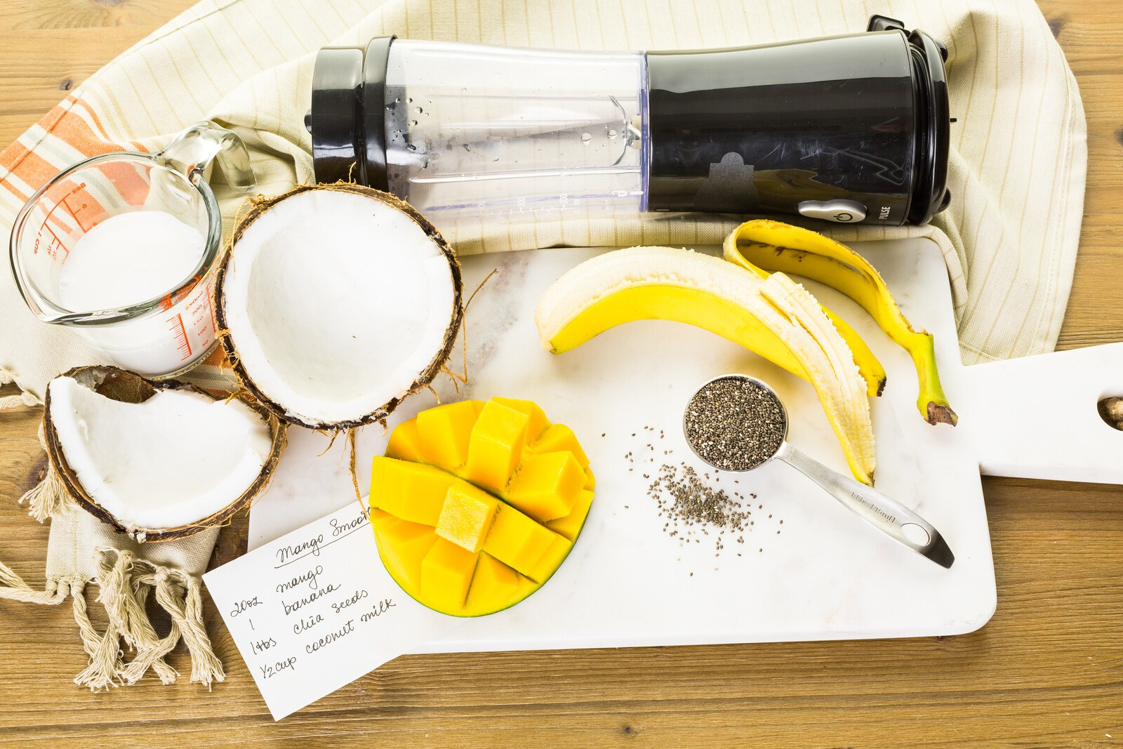 a black portable blender lying on a table surrounded with a slice of mango, a peeled banana and an open husk of fresh coconut