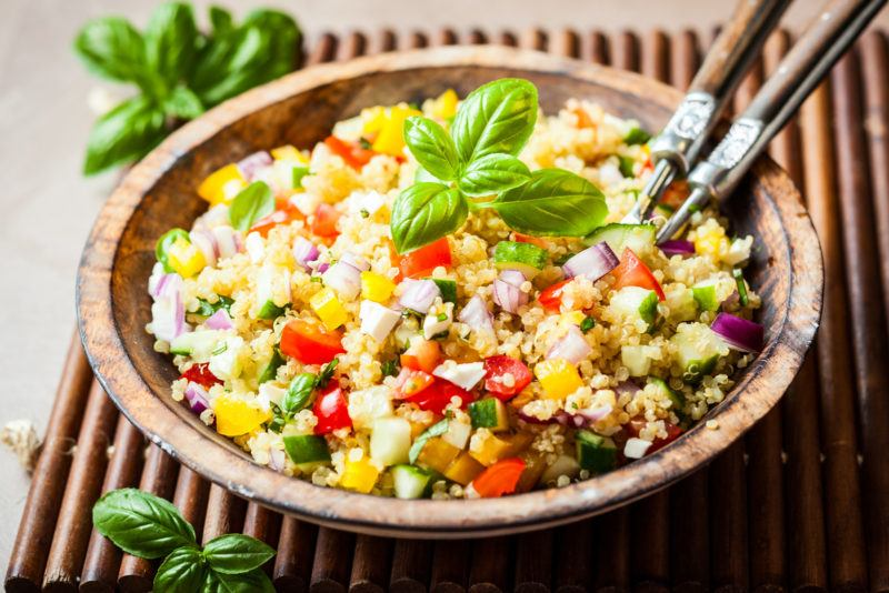 a plate of cooked quinoa topped with peppers, cucumber and fresh basil