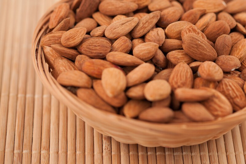 A small wicker basket filled with shelled almonds rests on a bamboo mat.