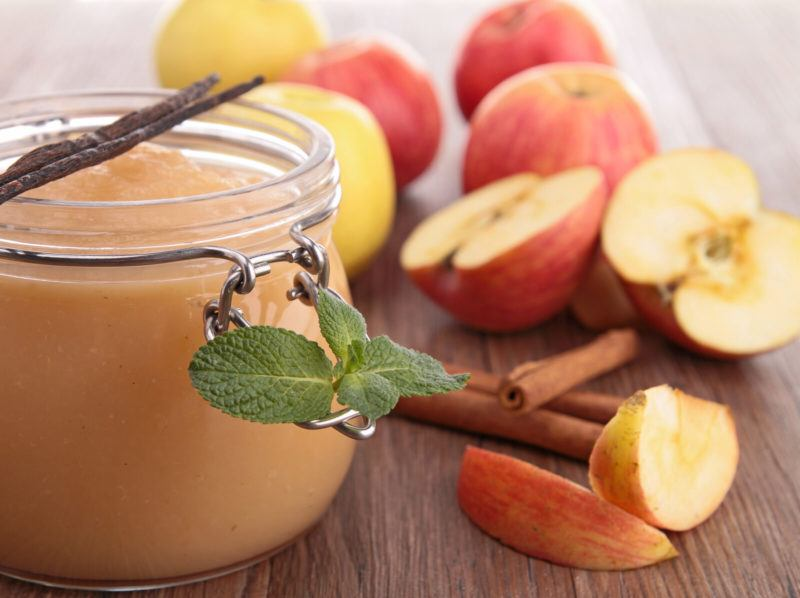 fresh apples, a jar of applesauce and cinnamon sticks on a wooden table.