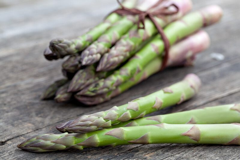 on a rustic wooden surface are three asparagus stems with a bundle of asparagus at the back