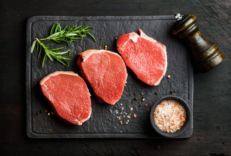 beef round eye steak raw on stone cutting board with coarse salt