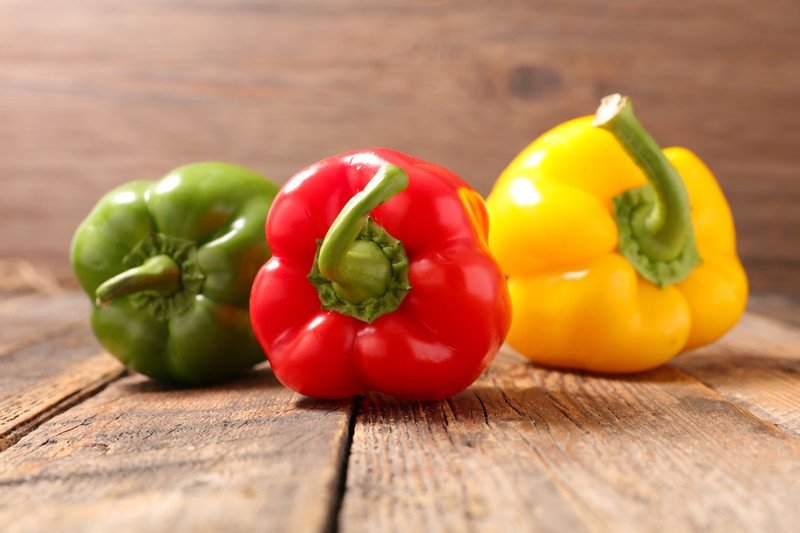 on an aged wooden surface are green, red, and yellow bell peppers