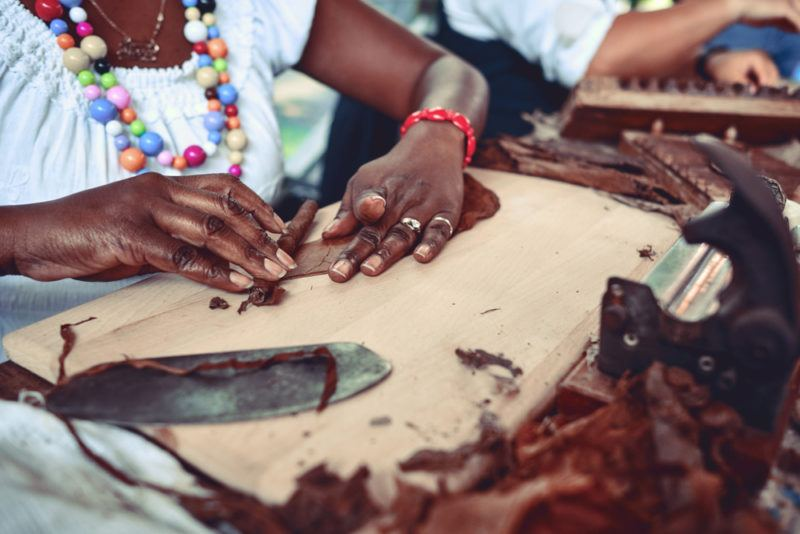 black woman hand rolling tightly wrapped dark cigar with tobacco leaves