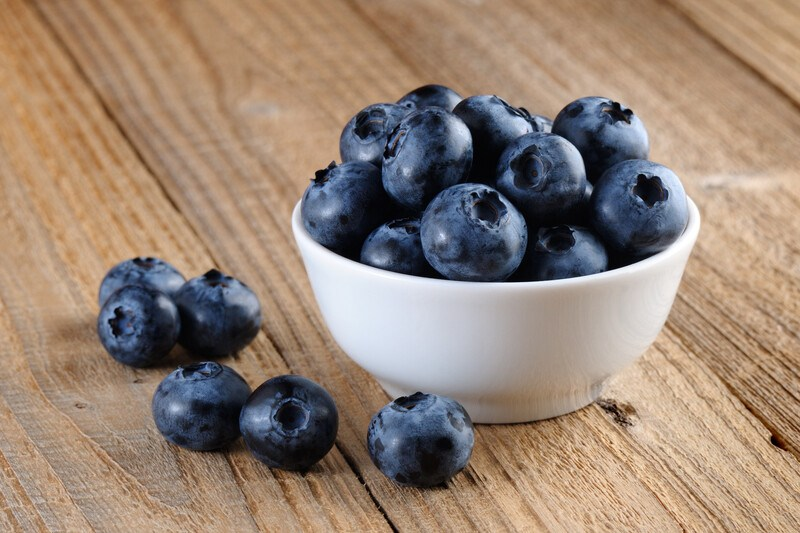 A white dish of blueberries and a few loose blueberries rest on a wooden surface.