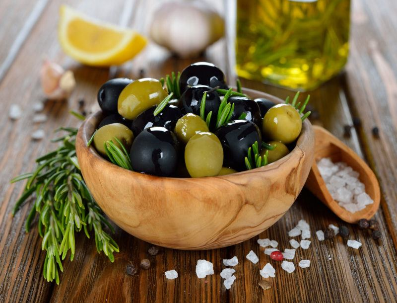 a bowl of olives with sprigs of rosemary on top of a wooden table.