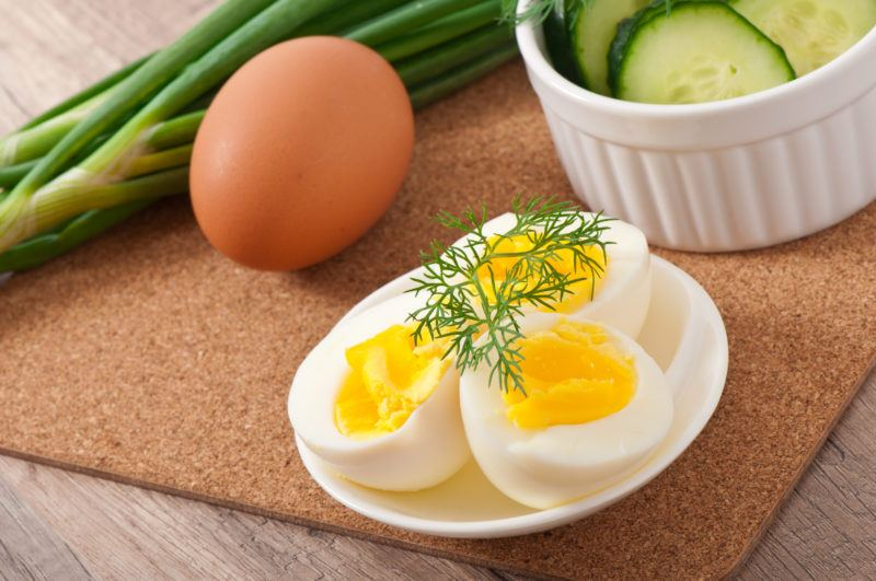 hardboiled eggs on a white dish, a bowl of sliced cucumbers, green onions and brown egg on a corkboard.