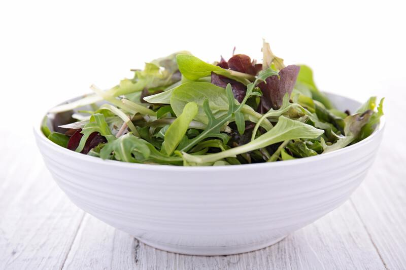 on a white wooden surface is a white bowl full of lettuce