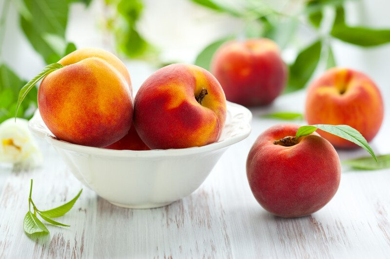 white wooden surface with a bowl full of fresh whole peaches, with loose peaches with leaves still attached around it