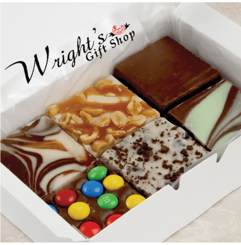 White cardboard box with 6 square pieces of fudge, white and milk chocolate swirl, peanut caramel, chocolate, M&M, Cookies and cream, and chocolate mint.  In the upper left side of the picture in black font it says Wright's Gift Shop