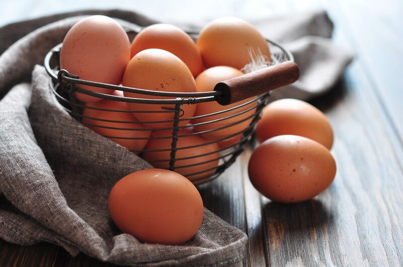 on a wooden surface is a wire basket full of brown eggs with a grey table napkin behind it and 3 loose brown eggs around it