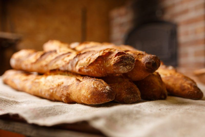 a stack of fresh baguette's on a table to represent where to buy fresh bread online