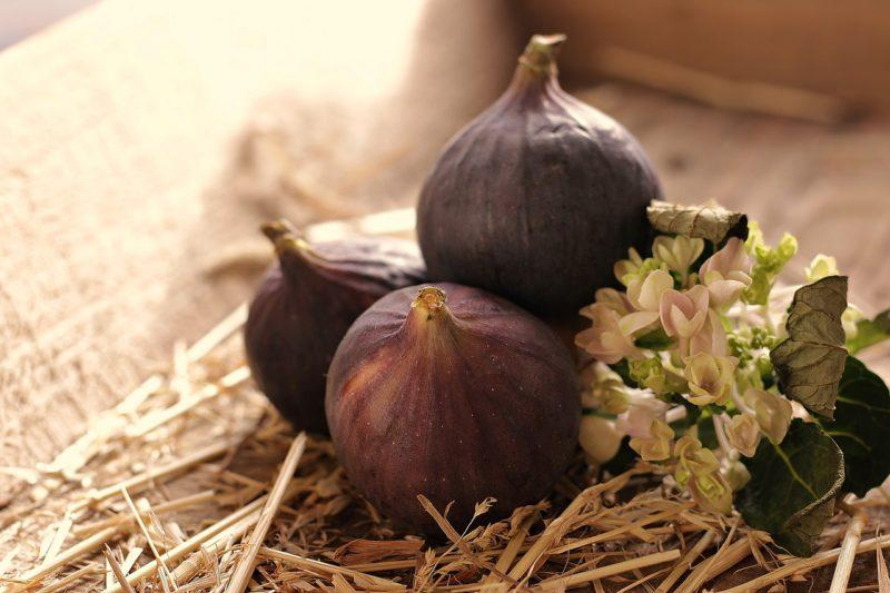 three figs and some flowers in a box to represent places to buy fresh figs online