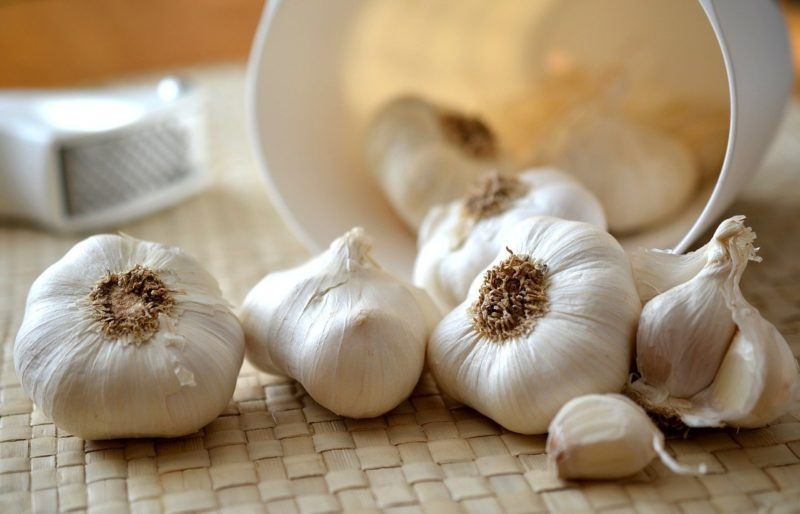 whole garlic spilling out of a white bin onto a table to represent where to buy fresh garlic online
